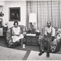 [African American man and woman sitting in chairs in their living room.]