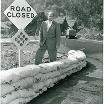 C. H. Lane Standing Along Street Lined with Sandbags