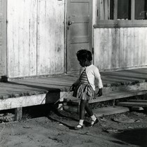 A child in front of World War II-era housing in Marin City, ...