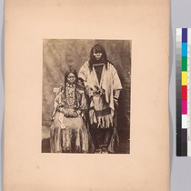 [Kalispel couple, full-length portrait, the man standing, the woman seated, facing front, ...