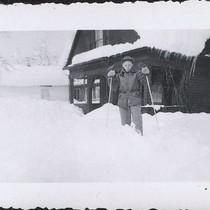 Boy skiing outside snow covered cabin