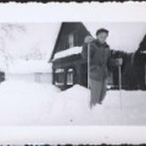 Boy posing on skiis outside of snow-covered cabin