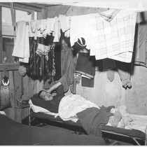 An evacuee resting on his cot after moving his belongings into this ...