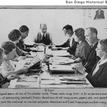 Group of people seated around a table clipping articles for the Works ...