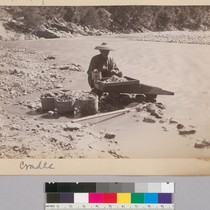 Cradle [Chinese man mining along river]