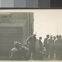 [Group of men, including Indians[?] or South Asians with turbans, outside building. ...
