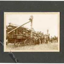 Agricultural workers posing in front of a large machine