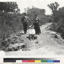 [2 women and a man on displaced earth along a road or ...