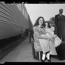 11 year-old actress Margaret O'Brien seated on suitcase holding a doll at ...