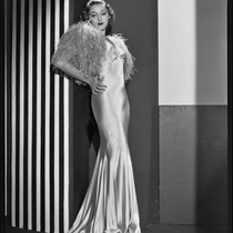Actress Kathleen Burke modeling an evening gown with ostrich wrap, 1932