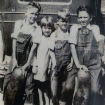 Earl R. Oatman and siblings as children holding gourds and fish