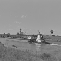 Tugboat pushing barge on slough, Walnut Grove