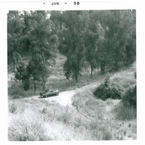 Car on Dirt Road, Taken from Hill Above