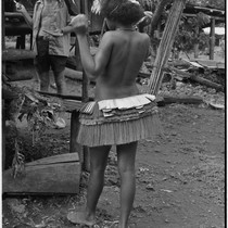 Adolescent girl, wearing short fiber skirt, Edwin Hutchins (in background) holding pen ...