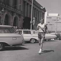 Photograph of of a runner from California State University, Hayward carrying the ...