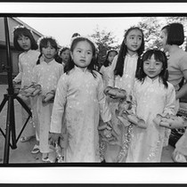 Ao dai clad children with flower head bands are holding decorative artificial ...