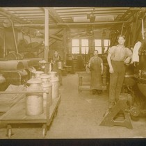 [Factory workers at machinery.]