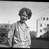 1/2 length portrait of Nita Carson standing on street smiling in Los ...