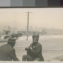 San Francisco. 1910. [Men sitting on wooden sidewalk, one Indian or South ...