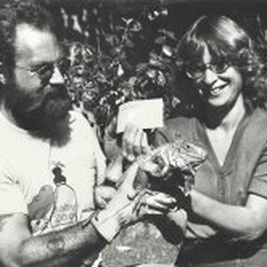 Man and woman holding an iguana