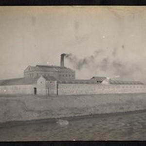 Large building with smokestack behind stone wall, China, ca.1904