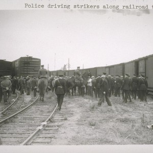 Police driving strikers along railroad tracks