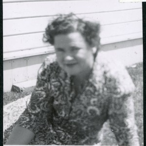 Photograph of Lucy Adams sitting on the grass in front of staff ...