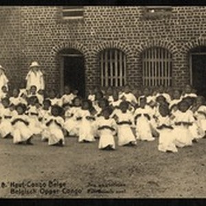 Missionary sisters standing outdoors among rows of kneeling young women, Congo, ca.1920-1940