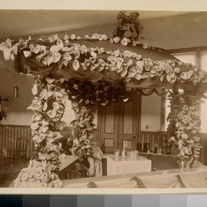 [Flower-covered exhibition booth with bar set up]