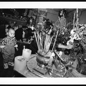 Woman adjusting flowers as baby stands by incense, 1999