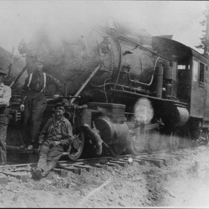Three men at the front of a lumber train locomotive, June 13, ...