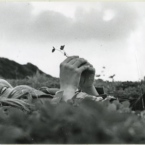 Student lying on ground in four-leaf clovers, holding a 4-leaf clover