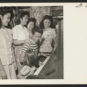 Gathered around the piano for some singing are several members of the ...