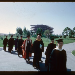 Convocation processional walking past Physical Sciences building