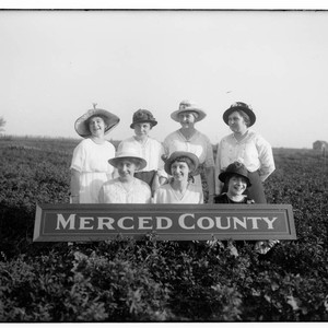 "Seven women with a ""Merced County"" sign"