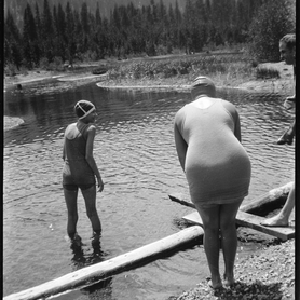 Two women in swim suits and caps wading in river