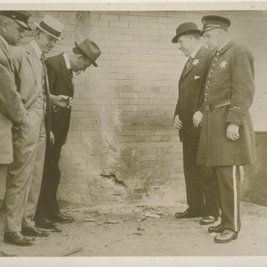 [Unidentified men, including police officers, inspect site of bomb explosion. Corner of ...