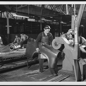 Interior view of an unidentified automobile factory showing workers on an assembly ...