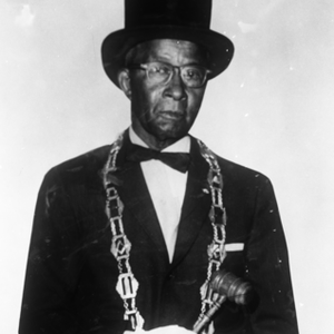 Portrait of mason wearing top hat and masonic chain holding gavel