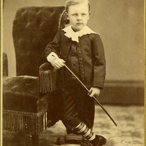 Portrait, Young boy standing by chair