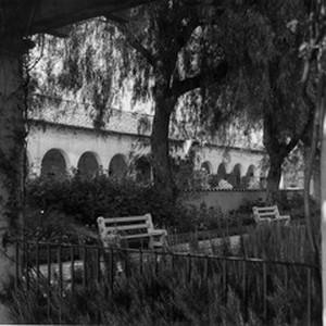 A view of the San Fernando Mission showing benches and trees next ...