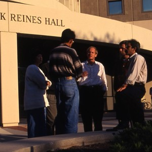 Students talking with faculty in front of the Frederick Reines hall.