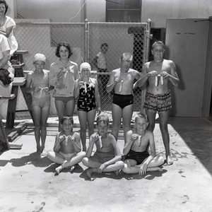 Children holding award ribbons at a swimming pool, Orange County, California: Photograph