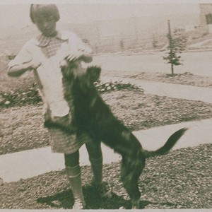 Frances Smith playing with a dog on Hartzell Street in Pacific Palisades