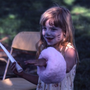 a child with cotton candy and a painted face