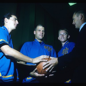 Varsity basketball coach Dan Rogers poses with players Dale Finney, Mark Nelson, ...