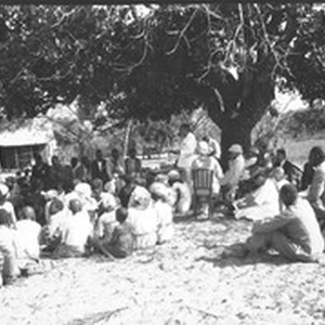 Swiss missionaries and African people sitting under a tree, southern Africa
