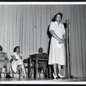 Anna Rosa Beverly (personnel supervisor) shown speaking in Home Office auditorium
