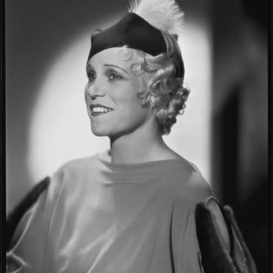 Peggy Hamilton modeling a dress with dolman sleeves and fur epaulettes and ...