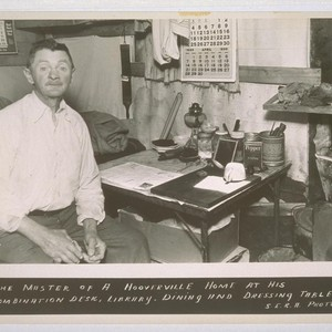 The master of a Hooverville home at his combination desk, library, dining ...